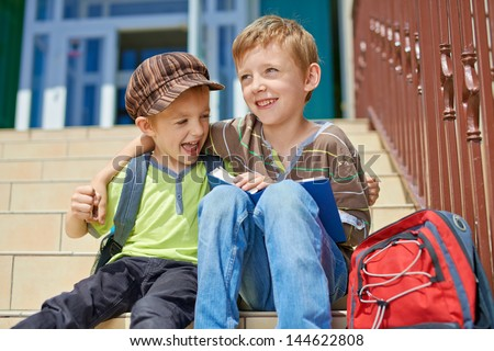Two happy brothers with book and backpack on stairs in front of school.