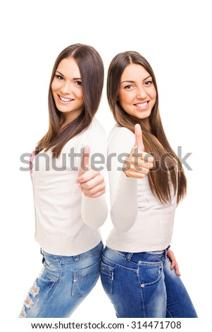 Two happy brunette teenage girlfriends smiling and gesturing thumbs up looking at camera isolated on white background. Two positive young women with long brown hair. Medium retouch, no filter. - stock photo