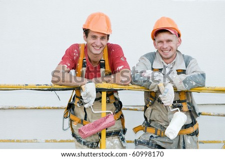Two happy builder workers  facade painters of high-rise building with rollers - stock photo