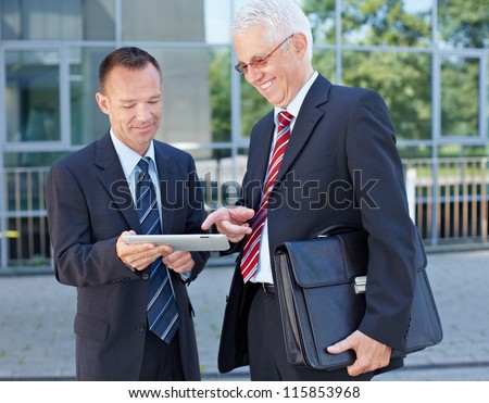 Two happy business men using a tablet computer outside the office - stock photo