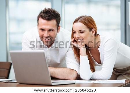 Two happy business people working on laptop in office - stock photo