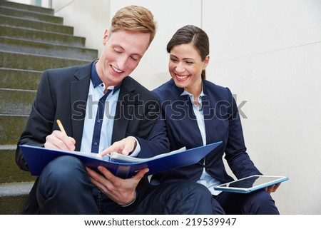 Two happy business people working together on files with tablet computer