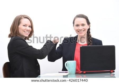 Two happy business women doing fist bump to celebrate - stock photo