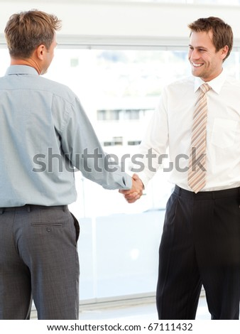 Two happy businessmen concluding a deal by shaking their hands standing in the office - stock photo