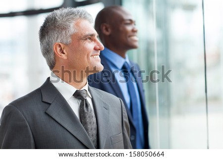two happy businessmen looking out the window - stock photo
