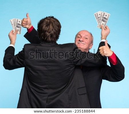 Two happy businessmen with dollar bills on a blue background