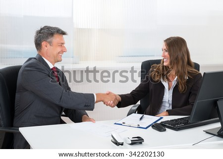 Two Happy Businesspeople Shaking Hands With Each Other In Office - stock photo