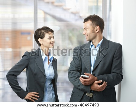 Two happy businesspeople talking in office lobby, looking at each other, smiling.