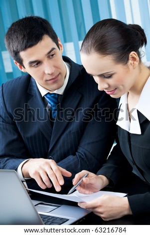Two happy businesspeople working together at office