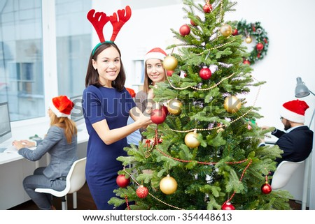 Two happy businesswomen decorating Christmas tree with red and golden bubbles