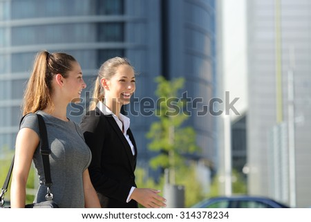 Two happy businesswomen walking and talking in the street with office buildings in the background - stock photo