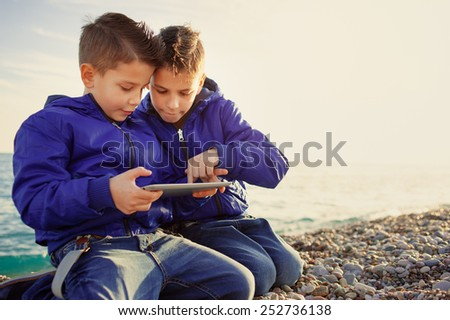 Two happy caucasian kids, brothers, playing together with tablet pc sitting outdoors at pebble beach against the sea - stock photo