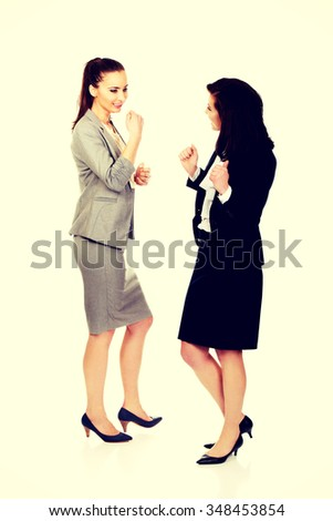 Two happy cheerful businesswomen making fists. - stock photo