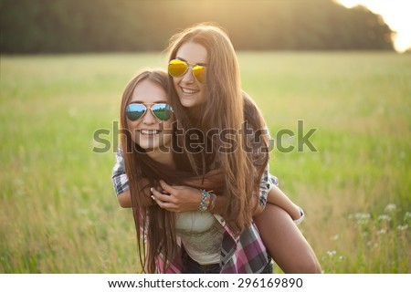 Two happy cheerful girl under the light of sunset. best friends - stock photo