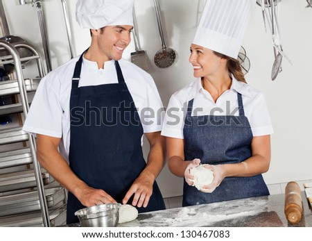 Two happy chefs looking at each other while kneading dough in commercial kitchen