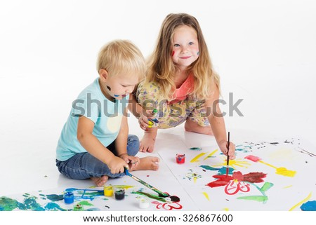 Two happy child boy and girl are having fun and drawing pictures by aquarelle paints, isolated on white, studio shot