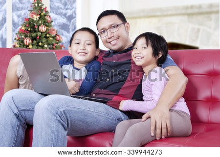 Two happy children and their father smiling at the camera while sitting on the sofa with laptop computer
