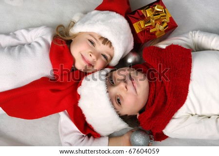 two happy children are in Santa Claus hats