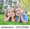 Two happy children are smiling and laying down on green grass in a yard outside with the sun shining for a summer or spring concept. - stock photo