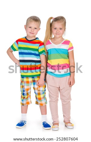 Two happy children are standing together on the white background