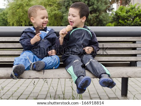 Two happy children, boys, friends or brothers, sitting on a bench eating ice cream.