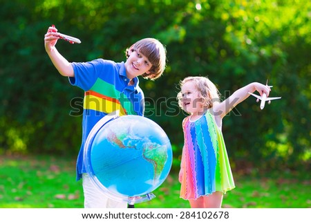 Two happy children, cute curly toddler girl and a smiling school age boy play with toy airplanes flying over the globe dreaming of traveling around the world. Kids fly and travel with airplane. - stock photo