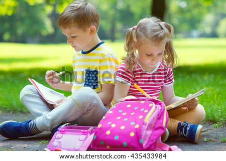 Two happy children  drawing in summer park - stock photo
