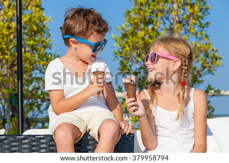 Two happy children eating ice cream near swimming pool at the day time. Concept healthy food.  - stock photo
