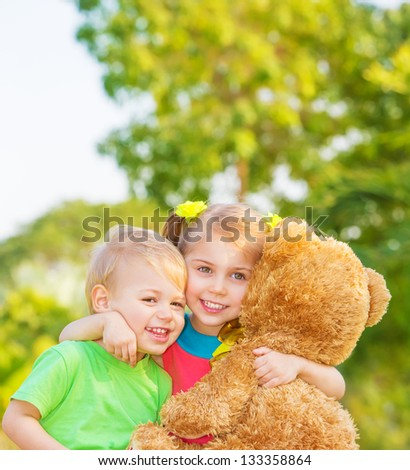 Two happy children enjoying big brown soft bear outdoors, brother and sister hugging, having fun on spring time, love and happiness concept - stock photo