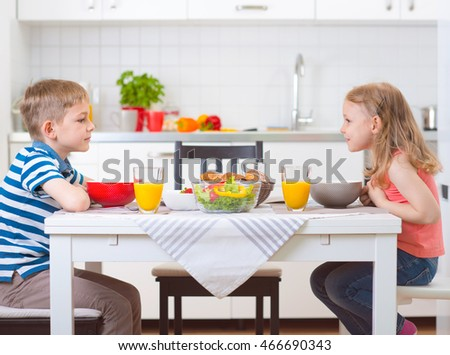 Two happy children having breakfast in kitchen at table