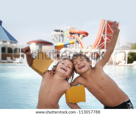 two happy children having fun in aqua water park - stock photo