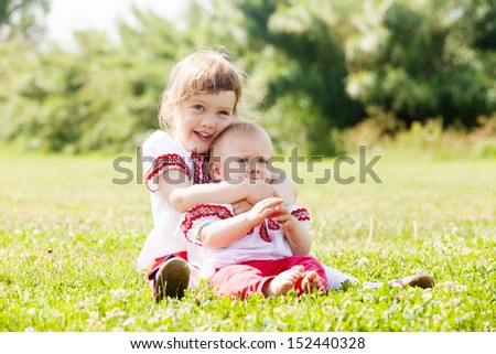 Two happy children in russian folk clothes on summer meadow