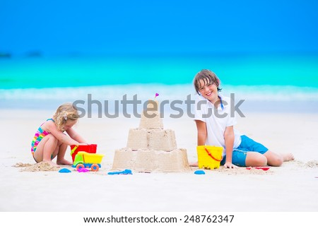 Two happy children, laughing boy and a little toddler girl in colorful swimming suit building sand castle and playing with toys on exotic tropical beach having fun at family summer vacation