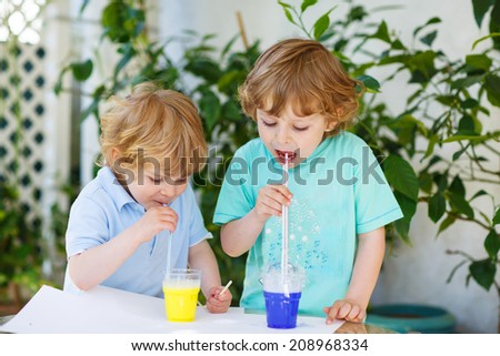 Two happy children making experiment with colorful soap bubbles and water, outdoors. - stock photo