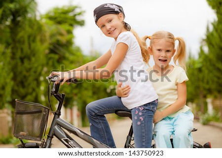 two happy children on a bicycle