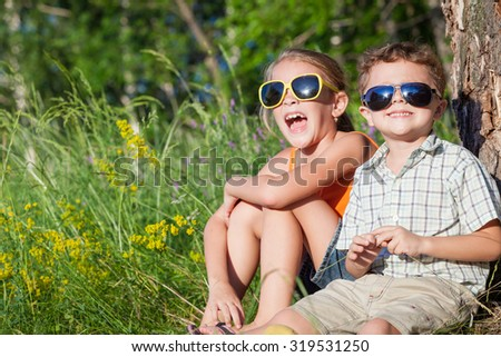 Two happy children  playing near the tree at the day time. Concept Brother And Sister Together Forever