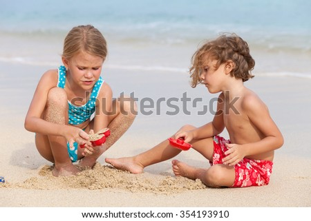 Two happy children  playing on the beach at the day time.