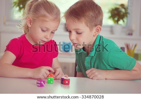 Two happy children playing with dices at home - stock photo