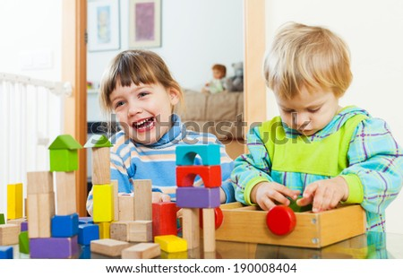 Two happy children playing with wooden blocks  in home interior - stock photo