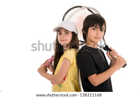 two happy children posing with tennis racquets on white background - stock photo