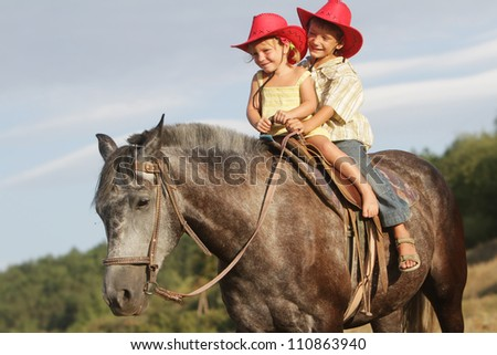 two happy children riding horse on natural background - stock photo