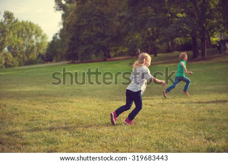 Two happy children running in park in sunset