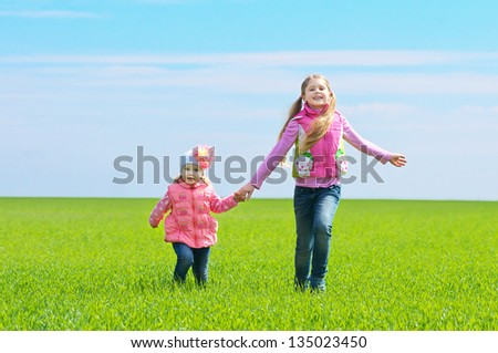Two happy children running on a green field - stock photo