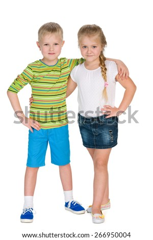 Two happy children stand together against the white background