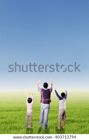 Two happy children standing on the meadow with their father and raise hands together to enjoy freedom