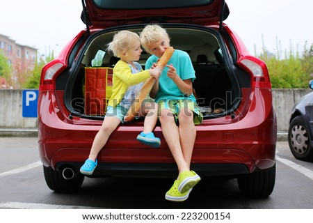 Two happy children, teenager boy and funny preschooler girl, brother and sister, sitting in the trunk of modern red car eating bread enjoying family weekend shopping in supermarket - stock photo