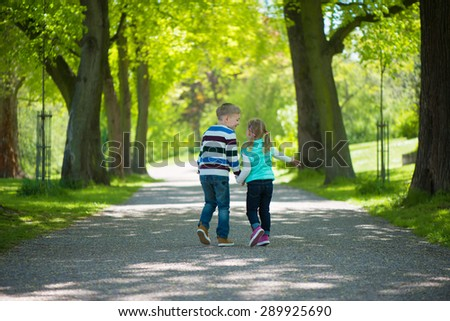 Two happy children walking in park. Holding hands - stock photo