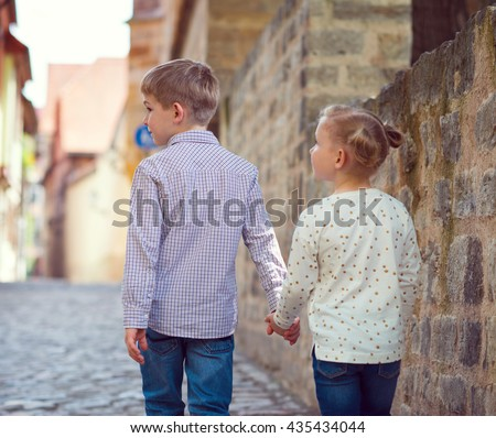Two happy children walking in sunny town - stock photo
