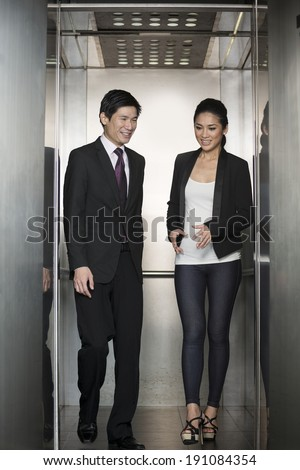 Two happy Chinese business colleagues walking out of an  elevator in a modern office building. - stock photo