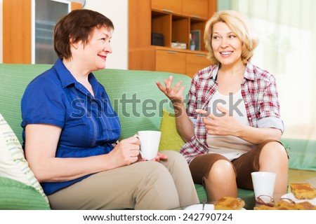 Two happy colleagues in years drinking tea and chatting during coffee break - stock photo